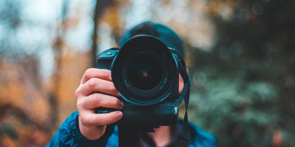Photographer holding black camera