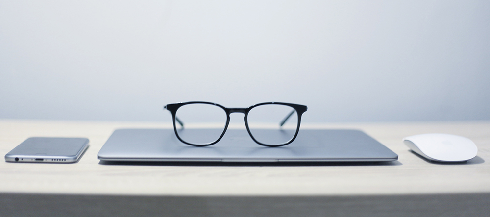 Laptop with glasses on top